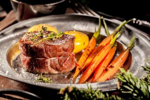 boar steak served on metal plate with carrots